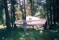 Корпус яхты подвешен между деревьями